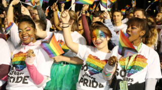 People in a crowd with their faces painted with rainbow patterns, waving rainbow flags