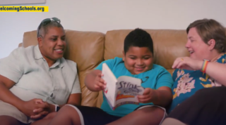 Two parents sitting on a couch with a child reading a book