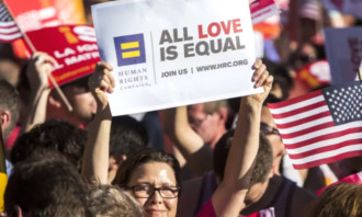 """A person in a crowd holds a sign that reads """"Human Rights Campaign. All love is equal."""""""
