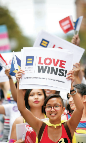 """A young person holds a sign that reads """"Human Rights Campaign. Love Wins!"""""""