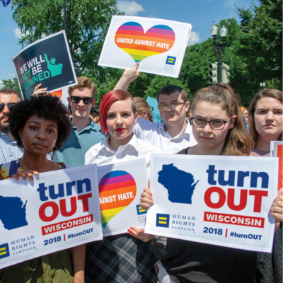 """A crowd of people holding signs that say """"Turn Out Wisconsin""""."""