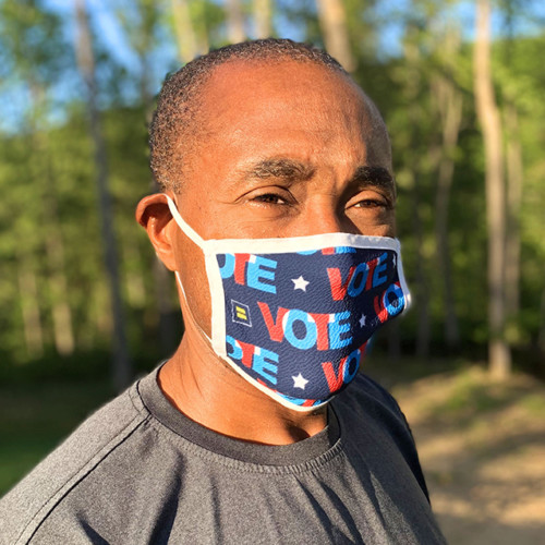 A person wears a mask that says VOTE and has HRC logos.