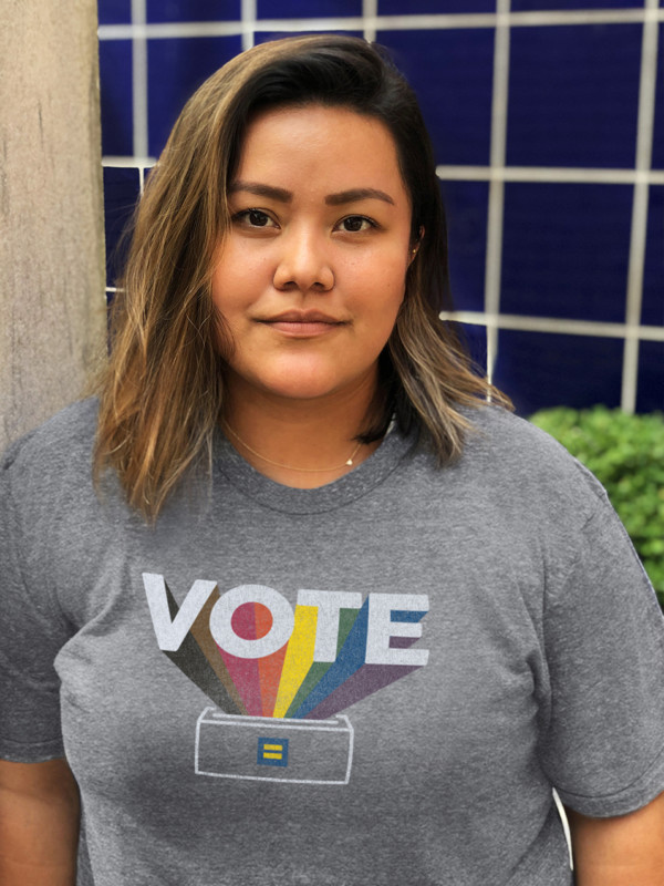 A person wears a shirt that says VOTE with rainbow colors.