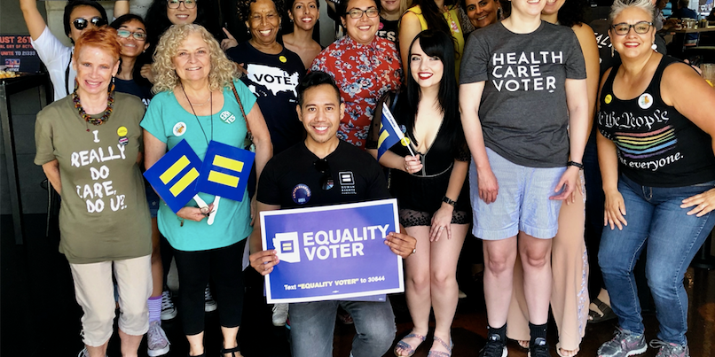 People gather together, holding signs that say equality voter and HRC flags