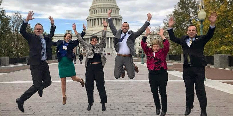 Five people outside the Capitol Building jumping in the air