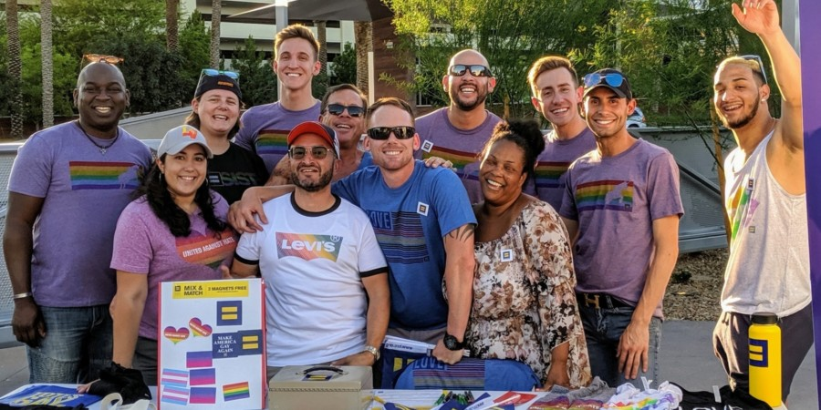 Group of people smiling at a pride booth