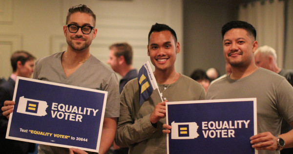 """Three men holding signs that read """"Equality Voter"""", with the HRC logo inside Pennsylvania map."""