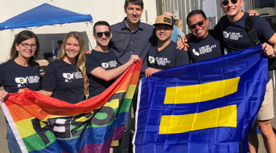 A group of people wearing equality voter t-shirts and carrying an HRC and rainbow flag.