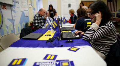 A woman makes calls at a table covered with HRC stickers.