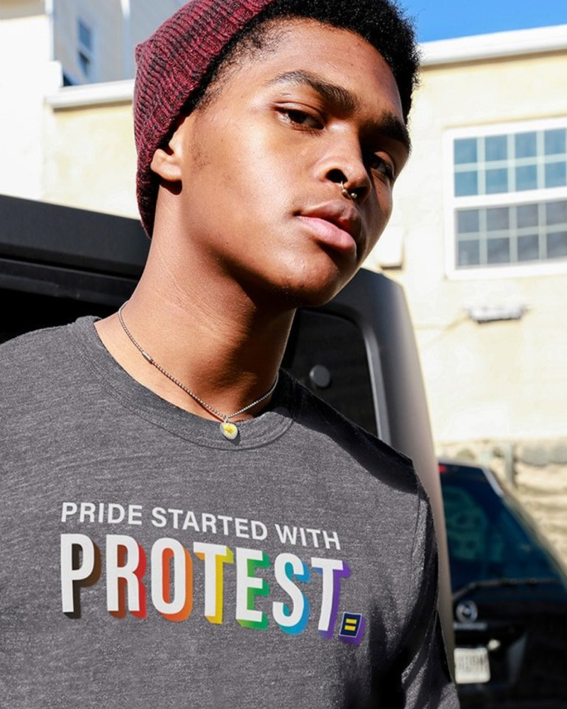 """A young Black man in a """"Pride Started With Protest"""" HRC t-shirt stares into the camera."""